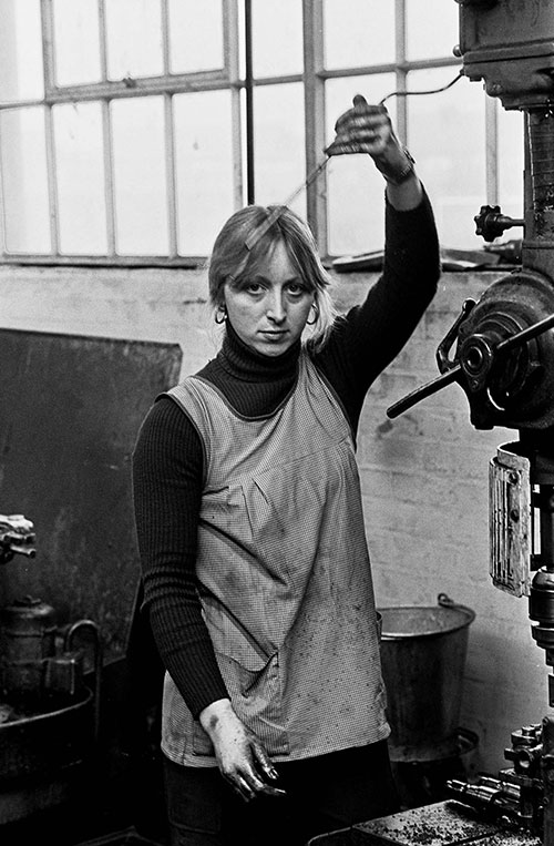 Girl at drilling machine with oil lubricant, Lee Howl pump factory Tipton  (1978)