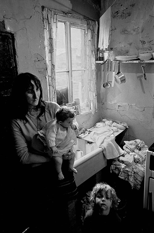 Mother and her children at the sink in their Salford condemned property,  (1971)