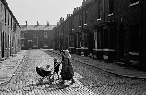 Family crossing the end of a Salford street of terraced houses,  (1969)