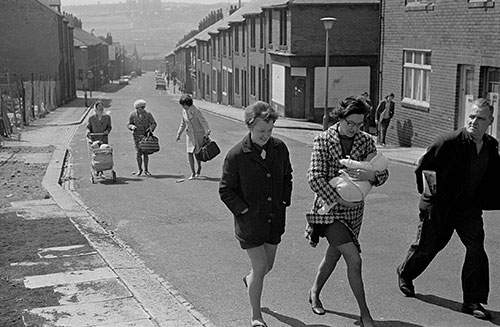 Family groups walk up a Byker street, Tyneside  (1970)