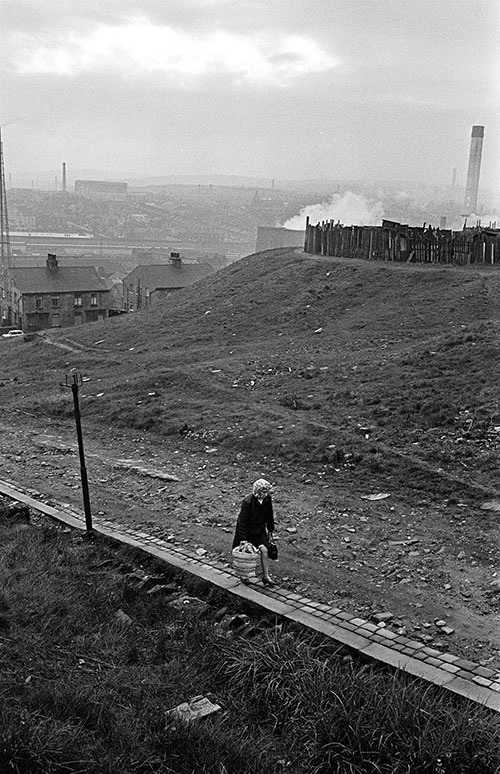 Woman climbing the hill towards home, Bradford  (1969)