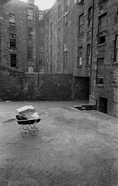 Pram and baby left out in a Maryhill tenement courtyard, Glasgow  (1971)