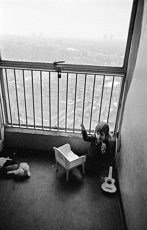 Child in her play area in the stairwell of the 13th floor of a tower block, Leytonstone  (1974)