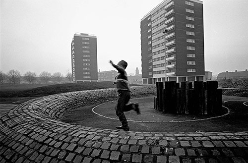 Boy playing by tower blocks, Birmingham  (1967)