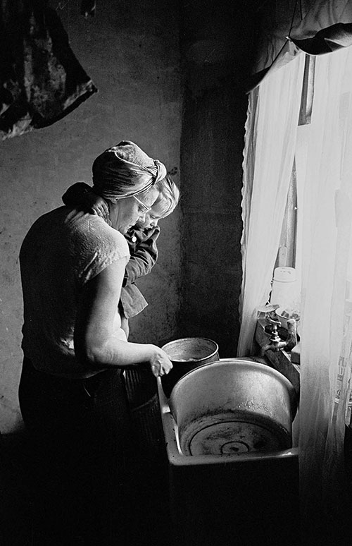 Mrs T and her baby at the sink in their Sheffield home,  (1969)