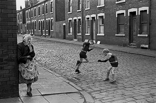 Elderly lady and children at the corner of a street of back to backs Leeds  (1970)