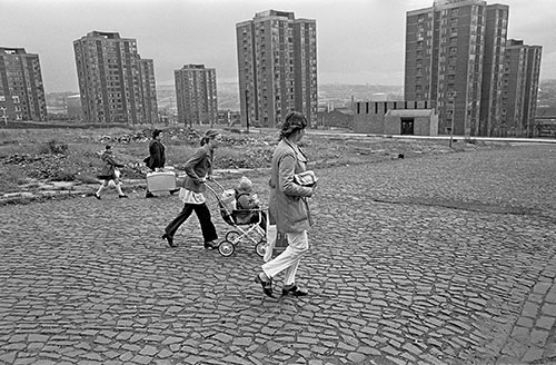 Family crossing slum cleared land by tower blocks, Newcastle  (1975)