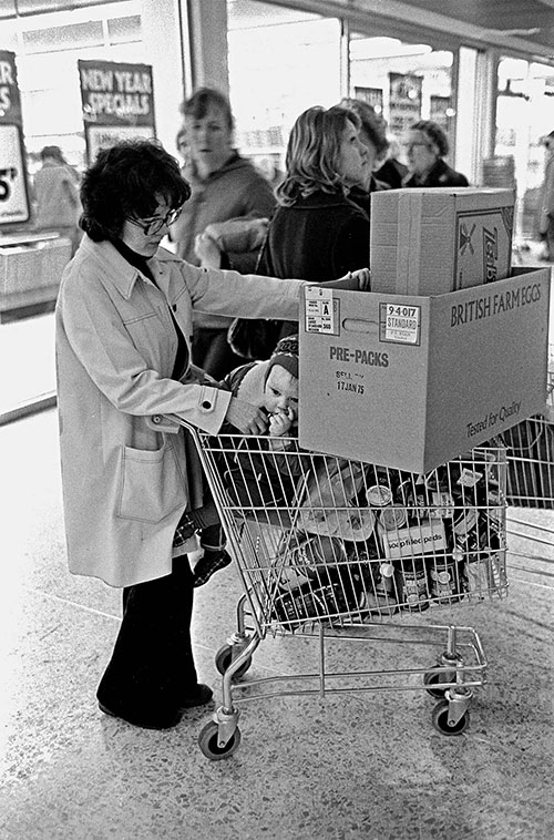 Mother and toddler after finishing a supermarket shop, Birmingham  (1975)