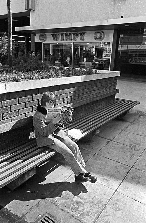 Teenager reading 'Journey into Mystery' in a shopping precinct Wolverhampton (1975)