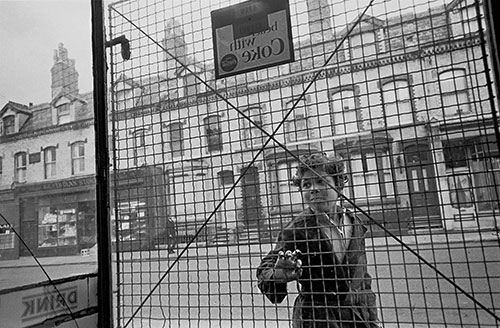 Child looks through the security wire in a Toxteth shop, Liverpool  (1969)