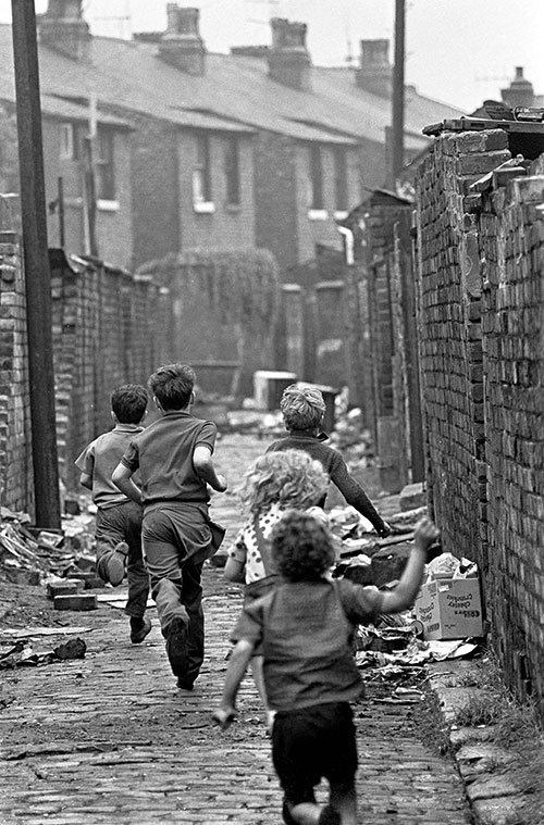 Gang of boys chase down a Manchester alleyway,  (1971)